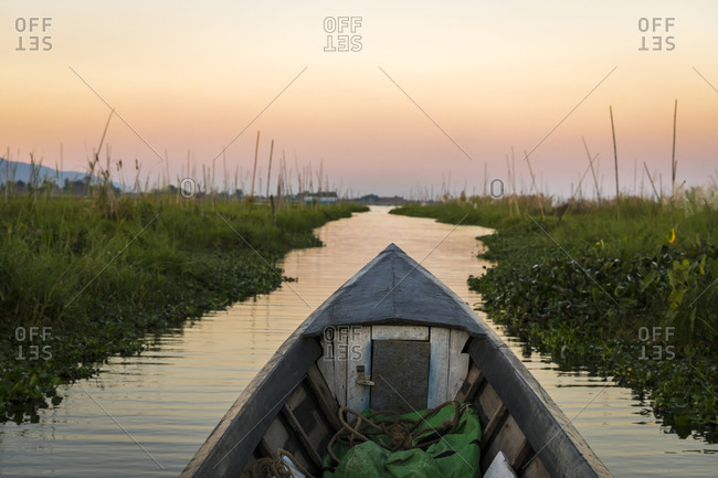 Motorboat on canal against sky during sunset, lake inle, myanmar