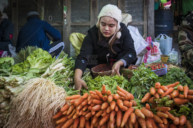 Nyaungshwe, shan, myanmar (burma) - january 21, 2018: burmese woman selling vegetables at market, nyaungshwe, myanmar