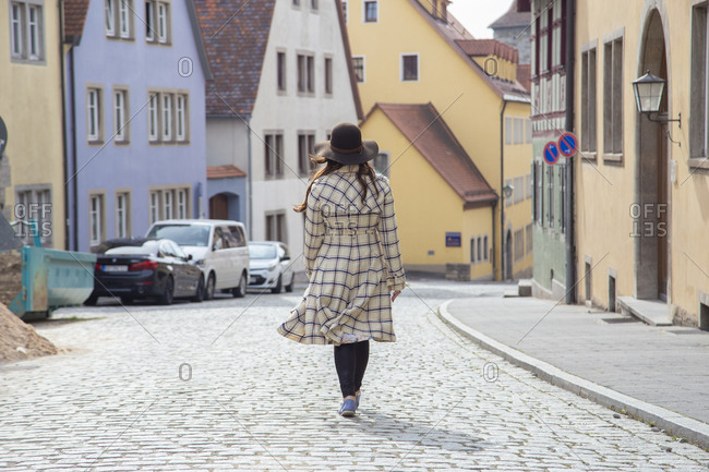 A woman wearing a long coat walking the streets of a medieval town.