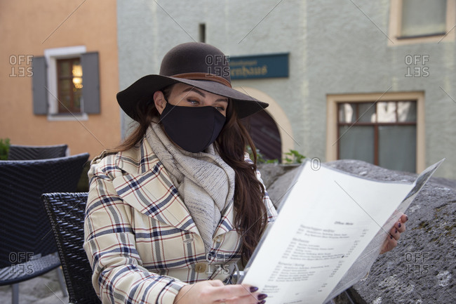 A young woman wears a mask and reads a menu at an outdoor cafe