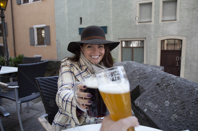 A smiling woman making a toast with a german beer