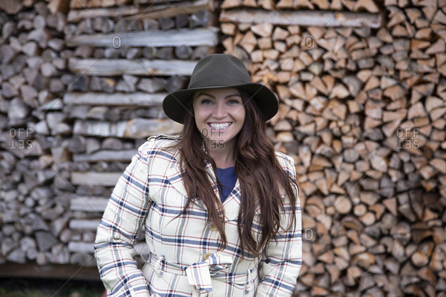 A young caucasian lady smiling at camera in front of a wood pile