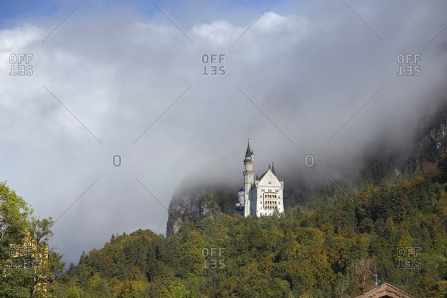 A side view of castle neuschwanstein through the clouds