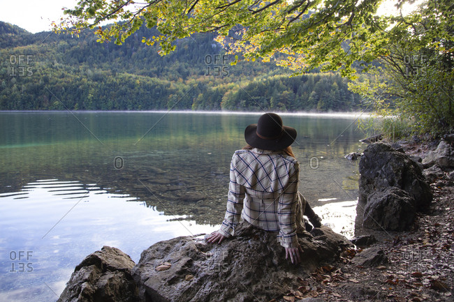 A woman sitting and relaxing under a tree next to an alpine lake