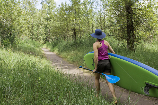 A young woman carries his standup paddleboard to the beach in oregon.