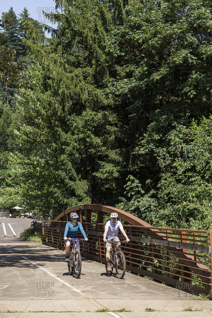 A couple ride their bikes on a bike trail in oregon.
