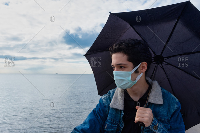 Young boy looking at the sea wearing a mask