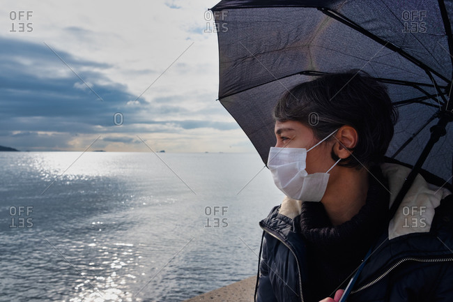 Woman looking at the sea wearing a mask