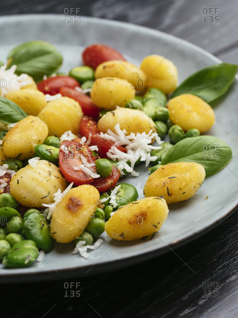 Fried gnocchi with fava beans, peas, tomatoes and vegan cheese