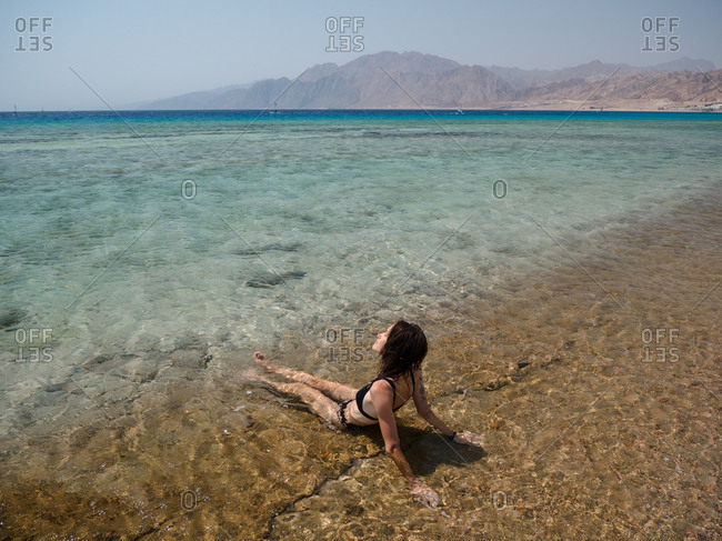 Young brunette woman relaxing in the sea with mountain backdrop