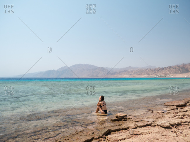 Young brunette woman relaxing on the beach near sea and mountains