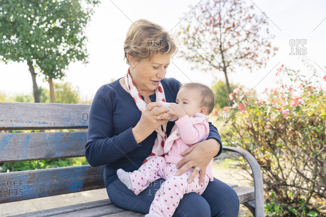 Grandmother feeding her granddaughter in the park