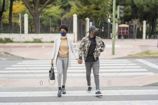 African wedding couple crossing the road hand in hand