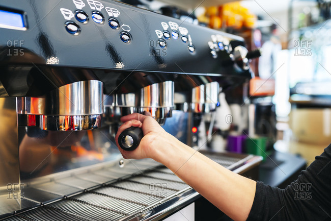 Woman's hand making coffee in professional coffee maker