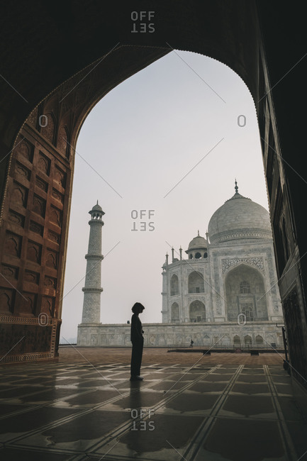 Young woman looking at taj mahal from inside kau ban mosque during sunrise, agra, india