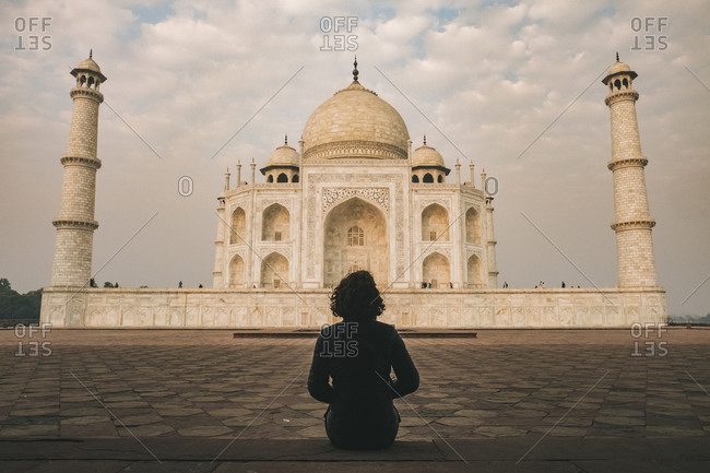 Young woman admiring taj mahal beauty during sunrise time on a cloudy day, agra, india