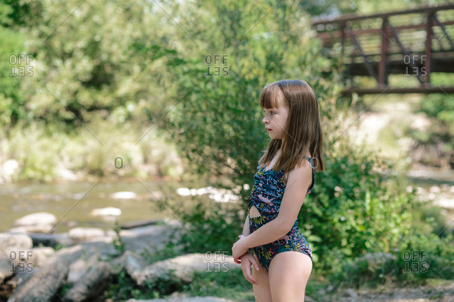 Young girl standing next to a stream on a sunny summer day