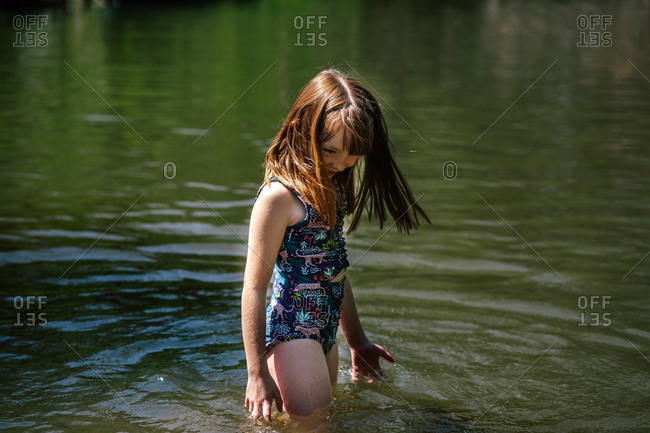 Portrait of a young happy girl playing in a river on a sunny day