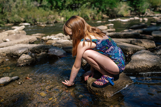 Young girl playing in a shallow stream on a sunny summer day