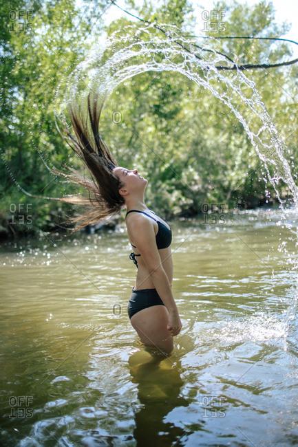 Vertical portrait of teen girl flipping wet hair in a creek