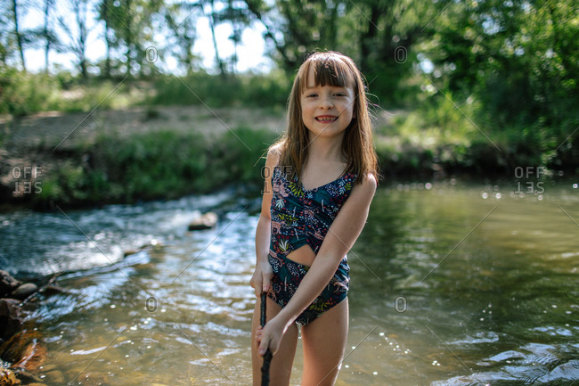 Happy young girl playing with a stick in a creek on a warm day