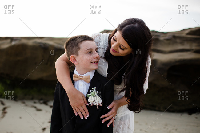 Newlywed mother hugging son on windansea beach in san diego