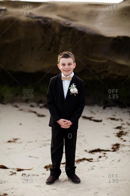 Nine year old boy in tux standing on beach in san diego