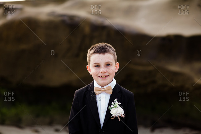 Nine year old boy in tux standing on beach in san diego