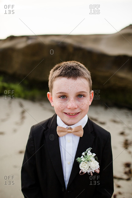 Close up of nine year old boy in tux standing on beach in san diego