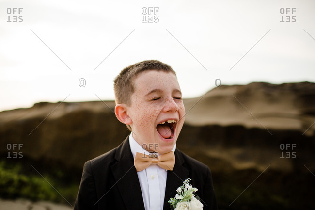 Nine year old boy in tux laughing & standing on beach in san diego