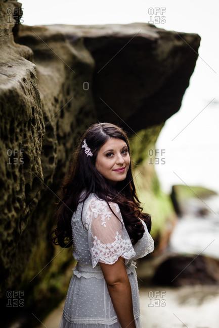 Newlywed bride standing between rocks on beach in san diego