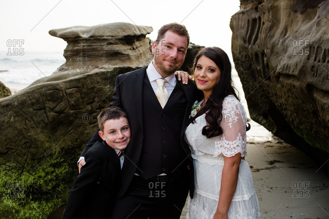 Newlyweds posing with nine year old son on beach in san diego
