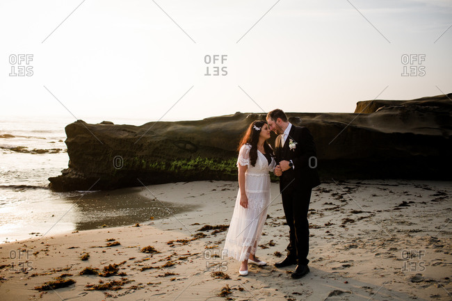Newlyweds on beach at sunset in san diego