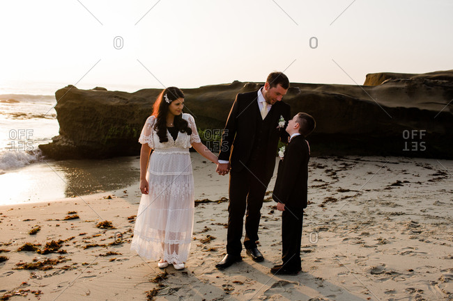 Newlyweds & son on beach at sunset in san diego