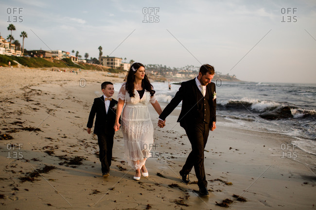 Newlyweds & nine year old son walking along beach in san diego