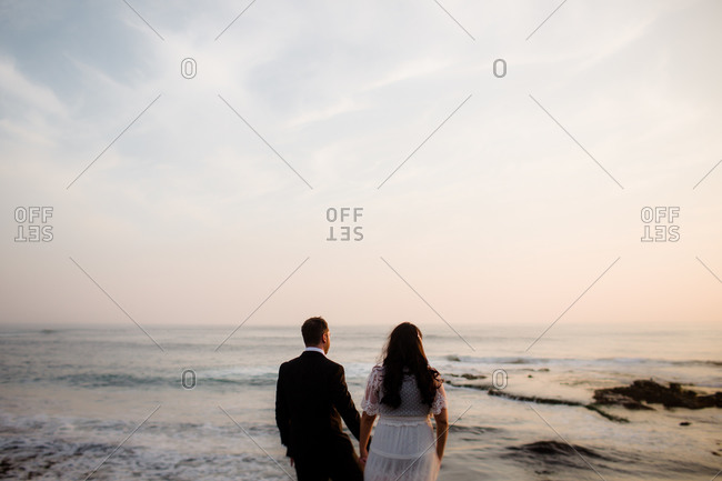 Newlyweds standing on rock at beach in san diego during sunset