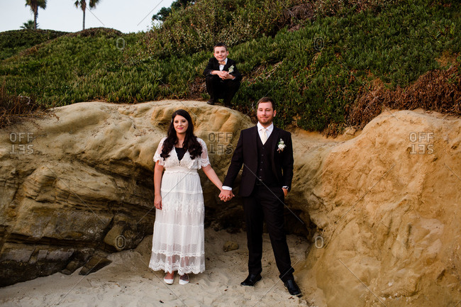Newlyweds & son posing next to rocks on beach at sunset in san diego