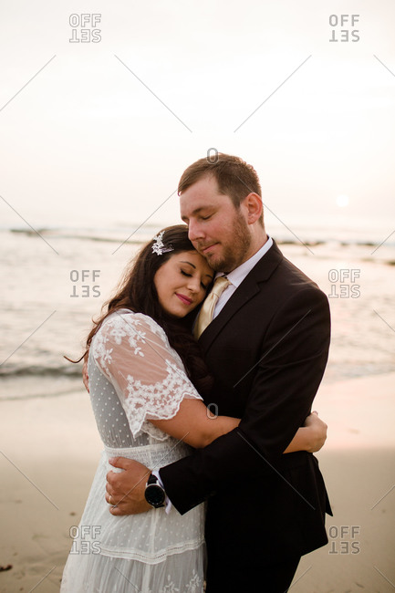 Newlyweds posing on beach at sunset in san diego