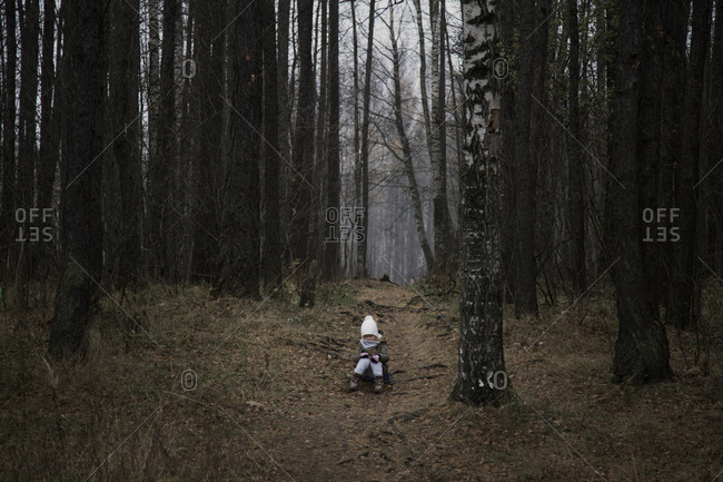 Little child alone in the autumn forest.