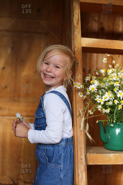 Image of a happy girl next to a bouquet of daisies.