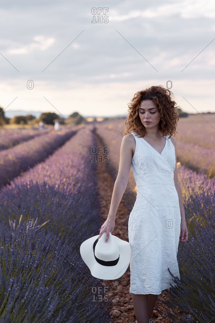 Woman with curly hair wearing a hat in a lavender field
