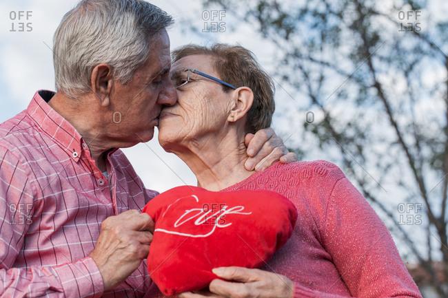 Loving elderly couple kissing tenderly