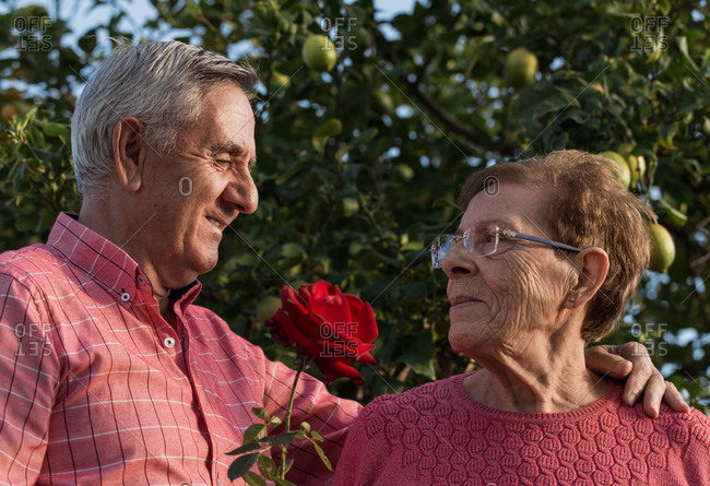 Romantic senior couple with flowers in garden