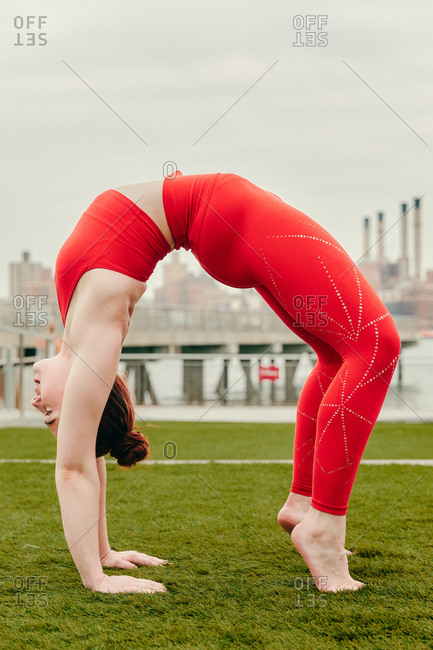 Young female athlete in a full wheel pose by waterfront in brooklyn.