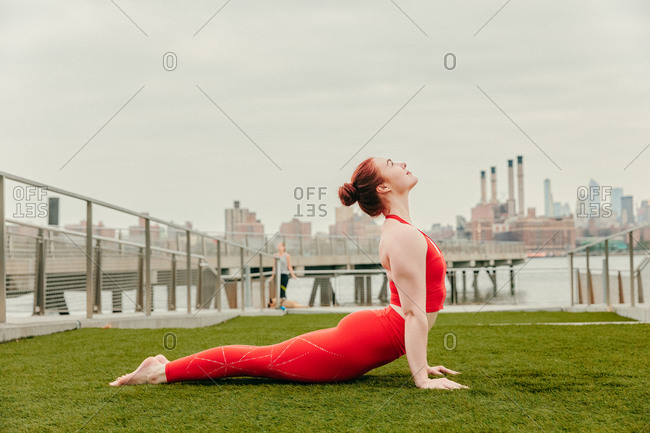 Young female athlete stretching by waterfront in brooklyn.
