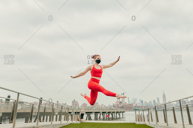 Young female athlete jumping mid air wearing face mask by waterfront