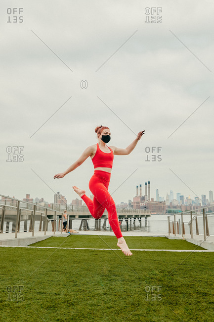 Young female athlete jumping mid air wearing face mask by waterfront.