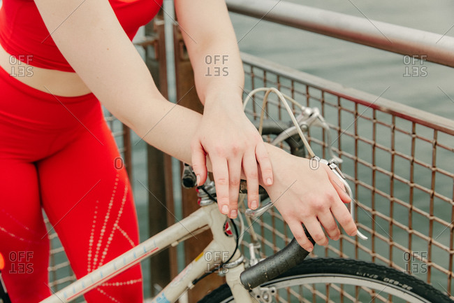 Young female cyclist's hands with bike by brooklyn waterfront.
