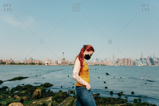 Young woman walking with facemask by brooklyn waterfront.