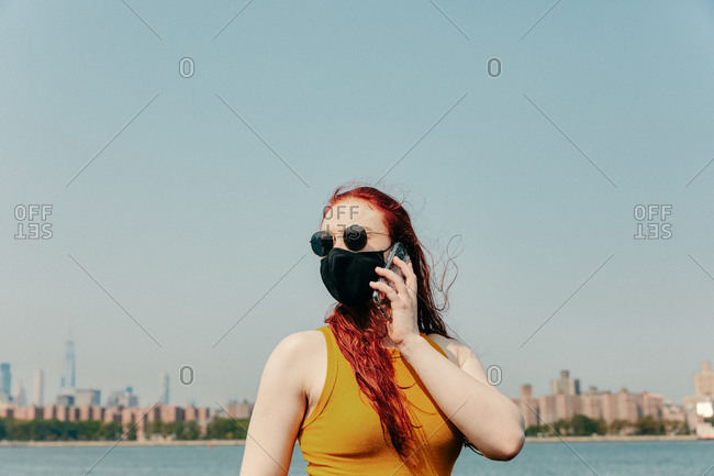 Young woman wearing face mask talking on phone by waterfront.